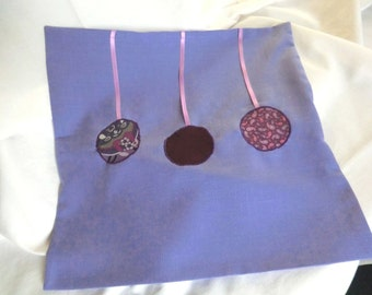 Purple pillow case with 3 different fabric circles on pink satin ribbon and hotel closure
