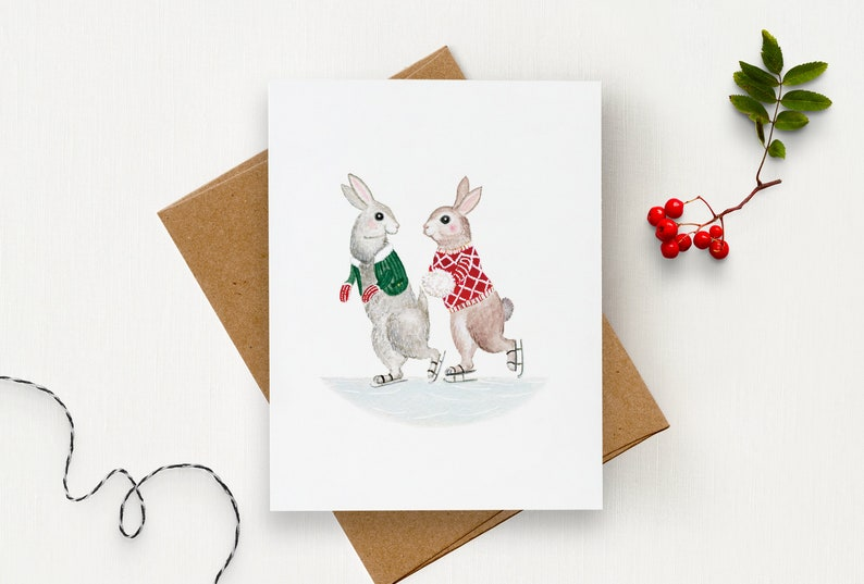 Greeting Card with Rabbits ice skating wearing wool sweaters  image 0