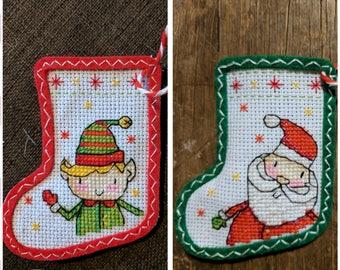 Two tiny Christmas stockings, one elf, one santa, Christmas tree decorations
