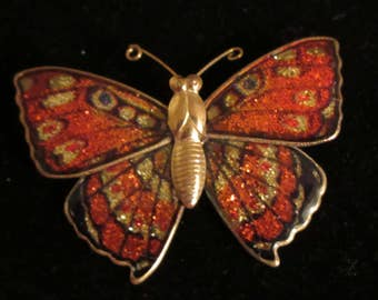 Lovely iridescent orange butterfly brooch / pin with gold tone hardware. Butterflies signify new beginnings. Great for any occasion!