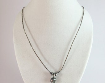 A handmade sterling silver necklace with the design of delicate flower pendant.