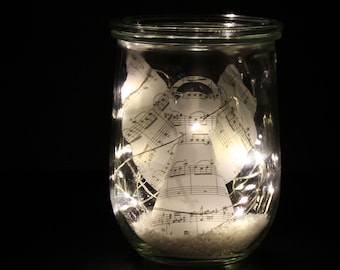 Wake-up glass with angel made of transparent paper, artificial snow and LED light chain