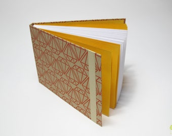 Small paper notebook with geometric patterns for writing or drawing (white pages)