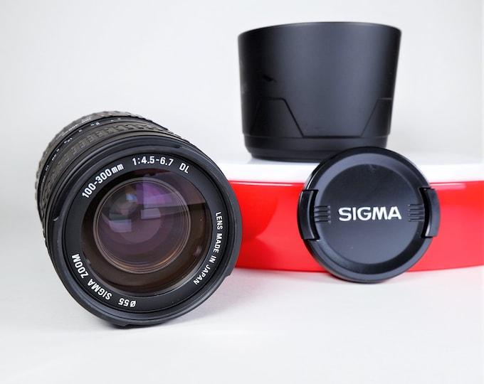 Sigma Minolta Mount AF 100-300mm f4.5-6.7 DL Zoom Lens for Minolta 35mm SLR Cameras - Lens Shade (Hood), Sigma Caps - Minty - Made in Japan