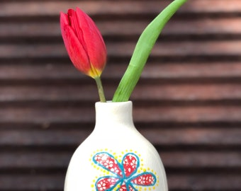 Handthrown budvase crafted from white stoneware clay. The exterior is decorated by hand with ceramic decals and painted with a floral design
