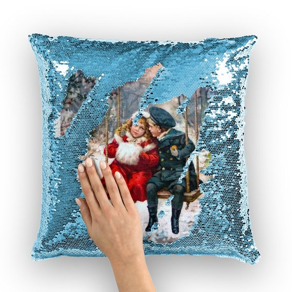 Pillow with shiny sequins in the shape of mermaid scales printed 1905 Snowy Winter. Girl and boy, swing on a swing surrounded by snowdrifts