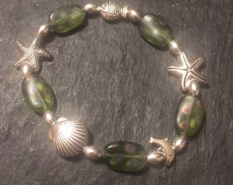 Silver plated ocean themed beads with green Czech glass. Stretchy bracelet