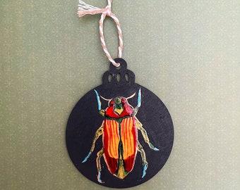 "Beetle enamel holiday ornament on 3.5"" wood round"