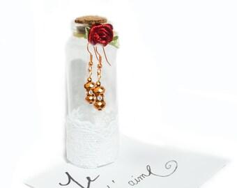 Gold crystal beaded earrings in glass bottle