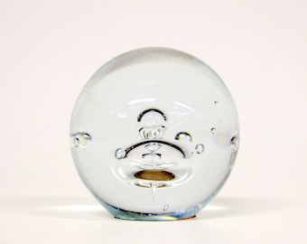Glass paperweight with a drop of
