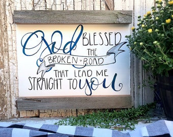 God blessed the broken road. Scroll sign
