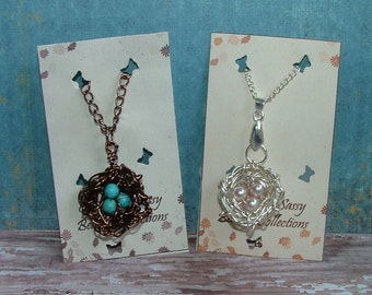 Bird nest necklaces, antique bronze with tortoise eggs or silver with white pearl eggs. Sold each seperate