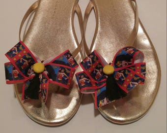 Shoe bows shoe accessories that look like Wonderful Woman with yellow homemade buttons and black tassels