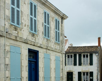 Rustic french town house with blue shutters, street scene in Ile de Re, France.