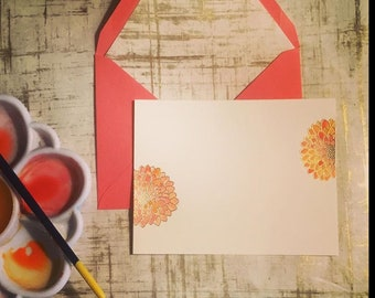Notecards with orange zinnias and lined envelopes.