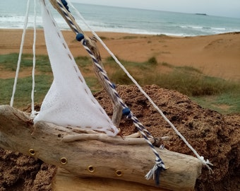 Medium decorative driftwood sailboat with white mainsail made out of gauze