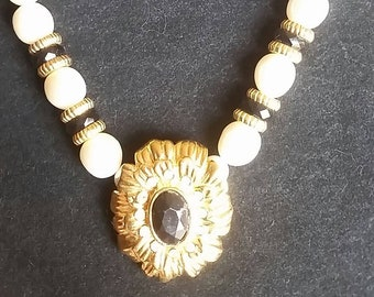 Vintage faux white pearl necklace with gold tone pendant.
