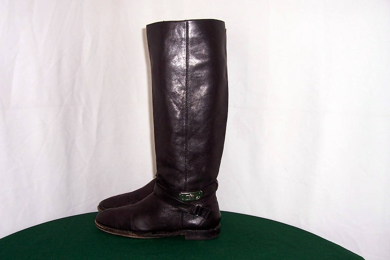 1ca05b2a54186 Coach Sz 7b Vintage tall black leather 1990s women flat riding boots with  wrap around strap and coach engraved buckle.