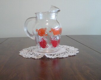 Vintage, juice pitcher with oranges and tomatoes.