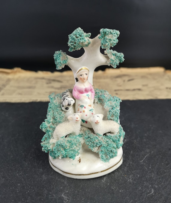 Antique Staffordshire figure, girl and sheep, shredded clay