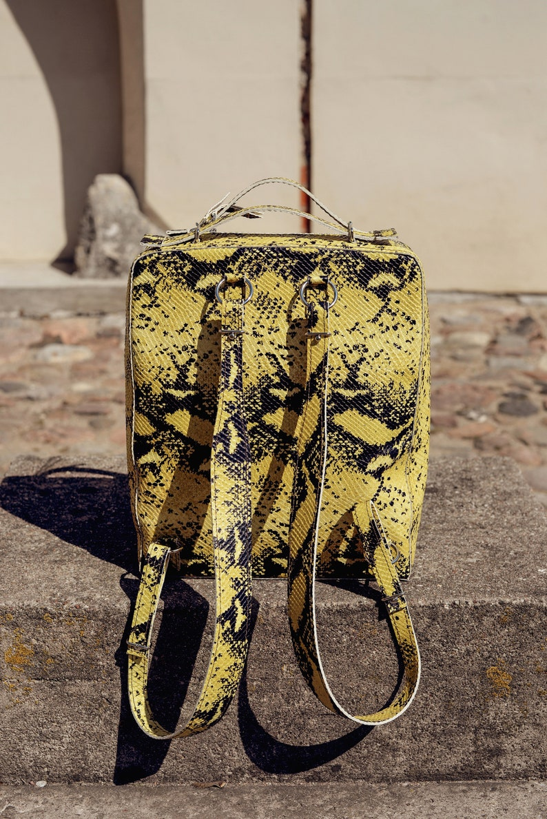 Leather backpack in yellow and black snake skin pattern imitation with adjustable straps Spacious structured animal print rucksack \u201eLupin\u201c