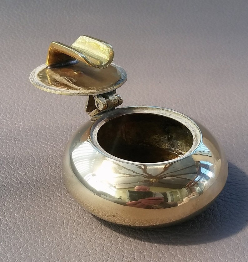 Brass vintage ashtray with lid with a resting place built into the underside of the lid for use when travelling