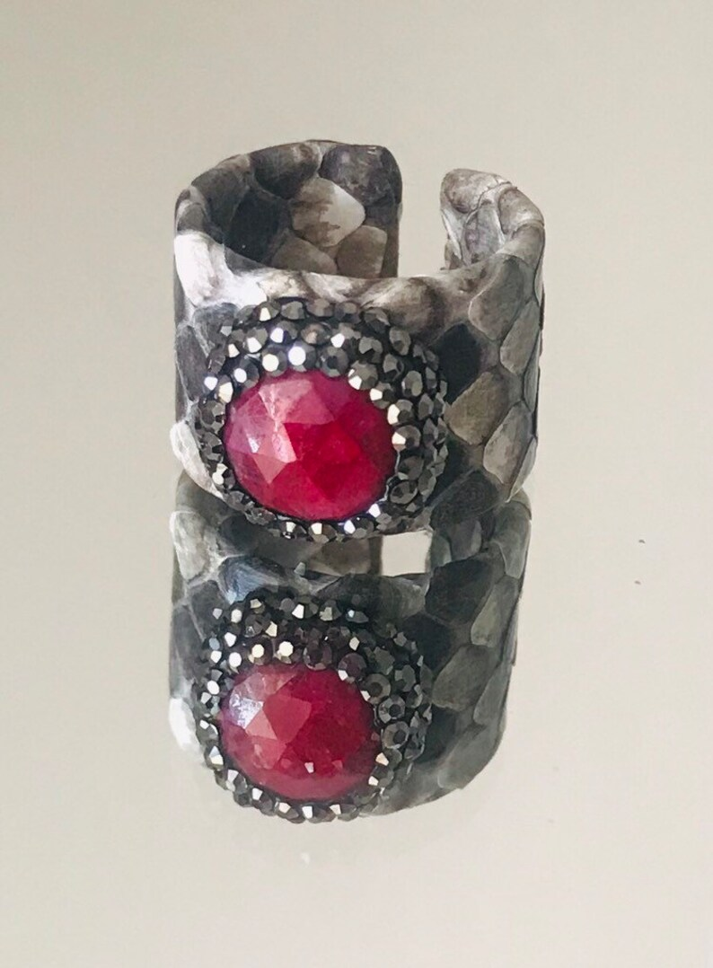 Faceted red garnet ring with druzys set in a  grey shaded python adjustable band.