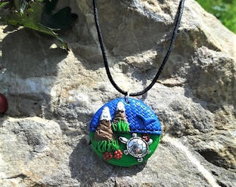 Round necklace with its little turtle in the mountains made of polymer clay.