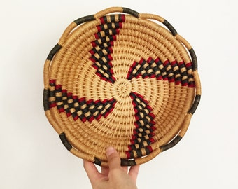 vintage woven round basket. wall hanging fruit bowl or plant holder catch-all in red green and tan.