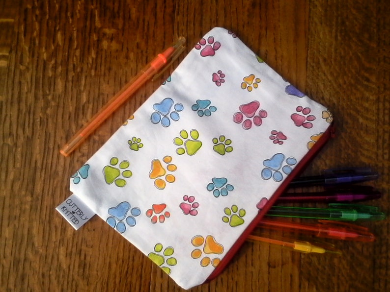 Multi colour paw prints on a white background pencil case with red zip