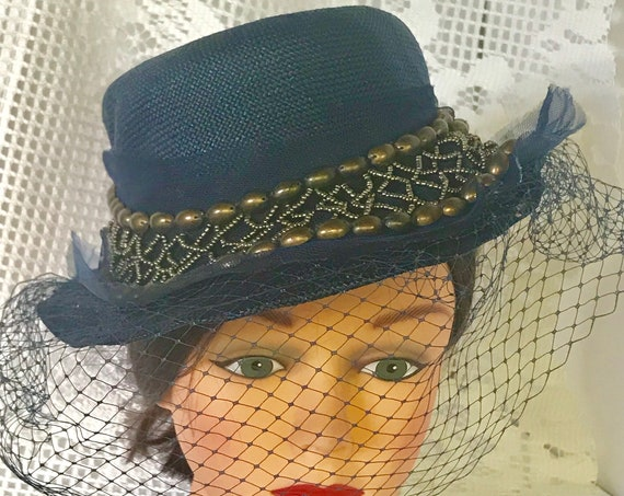 1980's navy blue women's Fedora hat, Riding hat . Re-enforced blue straw with 2 inch  brass gun-metal color adornment around hat blue veil