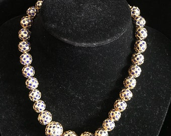 Golden necklace with interlayed blue glass.
