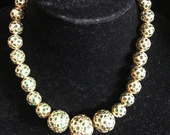 Golden necklace with interlayed green glass