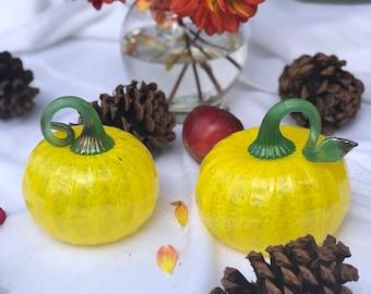 Small handblown mini pumpkins in vibrant yellow with green stems