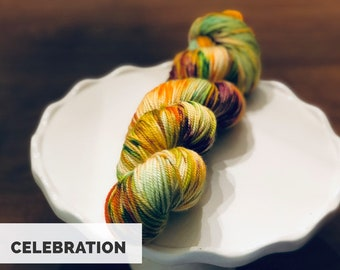 Celebration. Free Shipping. Hand dyed DK weight yarn on superwash merino wool & nylon. Ready to ship. Speckled. Purple. Orange. Green.