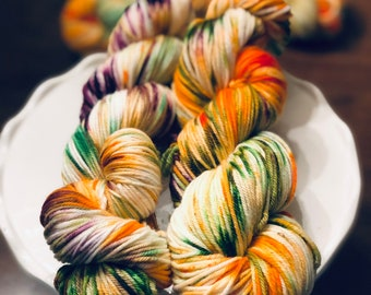 Celebration. Free Shipping. Hand dyed DK weight yarn on superwash merino wool & nylon. Ready to ship. Speckled. Purple. Orange. Green.
