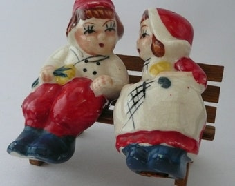 Vintage Boy and Girl Salt & Pepper Shakers Sitting on Wooden Bench