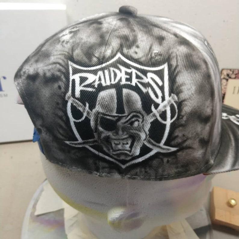 5fb68dbcb6251 Custom Airbrushed Oakland Raiders flat brimmed snapback hats.