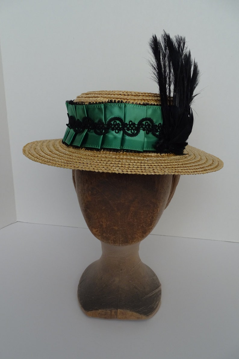 Victorian Style Hats, Bonnets, Caps, Patterns 1890s Reproduction Straw Boater with pleated green ribbon and black feather trim $123.50 AT vintagedancer.com