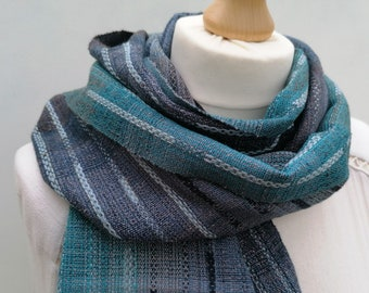 Unique light weight, all season scarf in cotton, merino wool and silk. In a palette of rich turquoise, greens and blues..