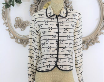 Lady like bow print vintage blouse size 6 made and designed by Nancy Crystal. Cream and black dainty top.