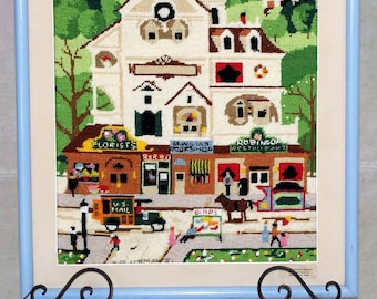 Vintage needlepoint picture. It is depicting a village building scene.  Beautiful handmade needlepoint.