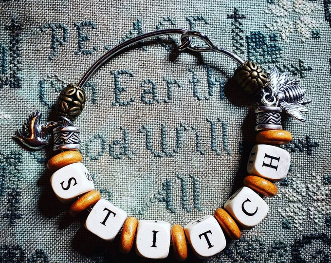 Bracelet with wooden and metal beads.  Bird charm and bumblebee bee charm. Word stitch in wooden beads