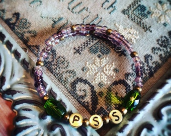 Expandable bracelet with word stitch metal beads and glass beads