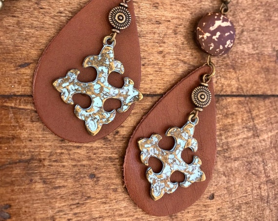 Antique Bronze Cross with silver patina earrings over brown leather.