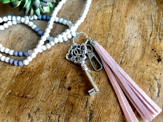 Long Powder Blue Bead, Cream Bead Lanyard and Badge Holder with Large Silver Key and Pink Tassel.
