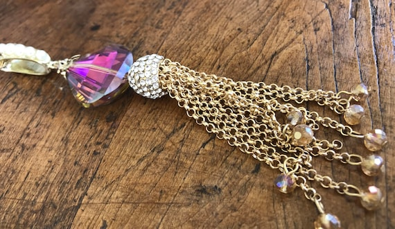Long gold chain with gold chain tassel. Purple crystal and pearl details.?
