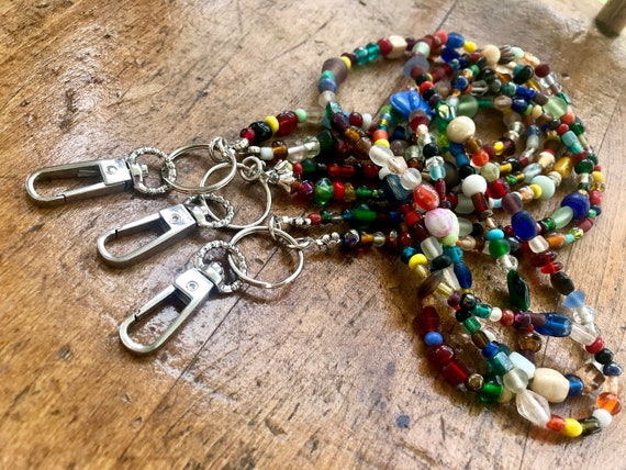 Bright, beaded, long lanyard with silver clip.