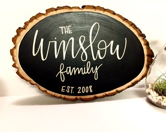 Custom family name wood slice - chalk paint with hand lettered gold writing. Year established with last name.