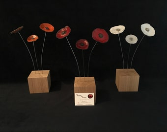 Three ceramic flowers on square oak base